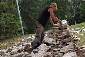 Un muretier au travail pour la restauration d'un mur en pierres sèches